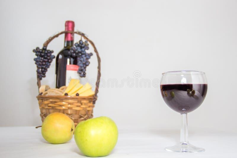 杯红葡萄酒,供食用黄绿色苹果、葡萄和乳酪在篮子在白色模糊的背景 免版税库存照片