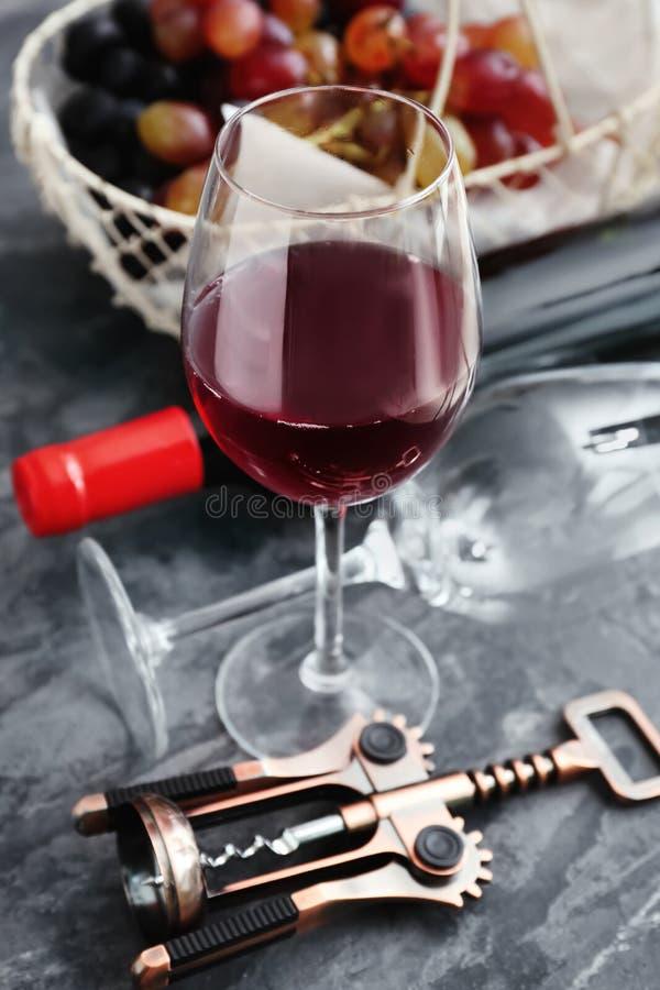 杯红酒和拔塞螺旋在桌上 库存图片