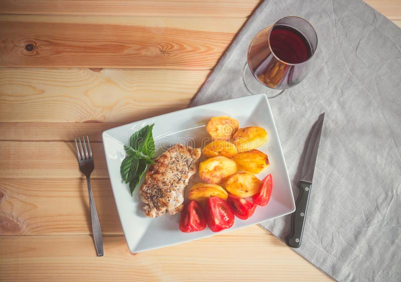 杯红酒和烤猪肉用烤土豆在桌上 免版税库存照片
