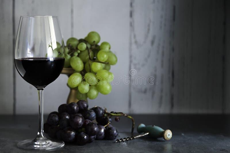 杯红酒拔塞螺旋和葡萄群 免版税库存照片