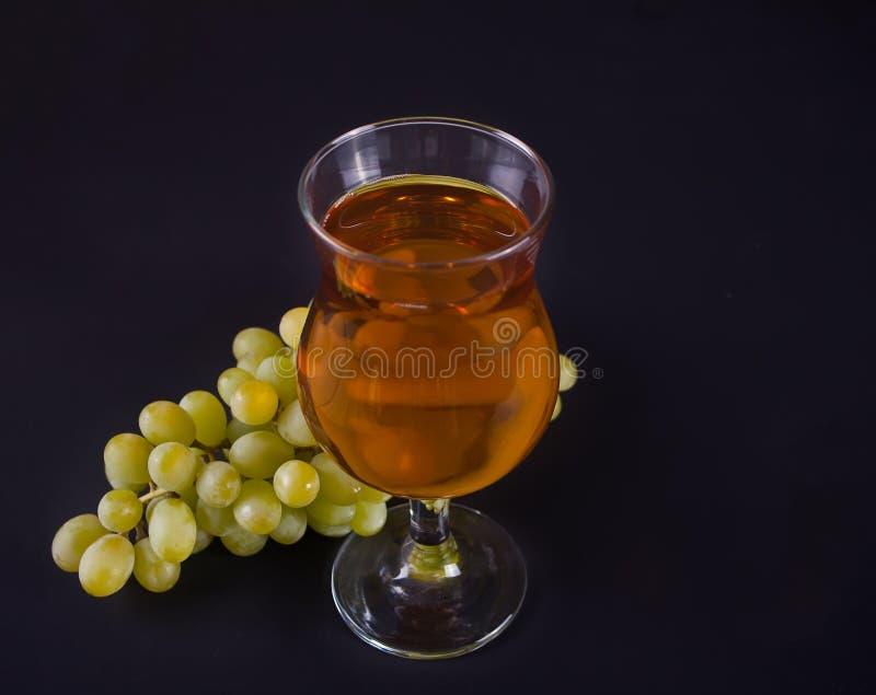 杯绿色葡萄汁或白酒与葡萄在黑背景 免版税库存照片