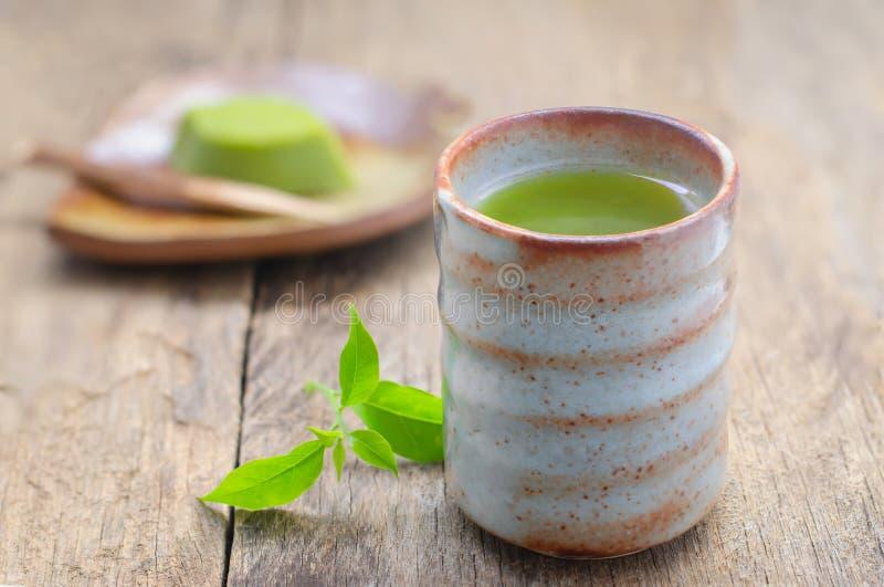 杯绿茶用在木桌上的日本点心 免版税库存照片