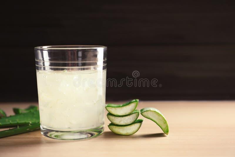 杯芦荟维拉汁液和绿色叶子在木桌上反对黑暗的背景 免版税库存图片