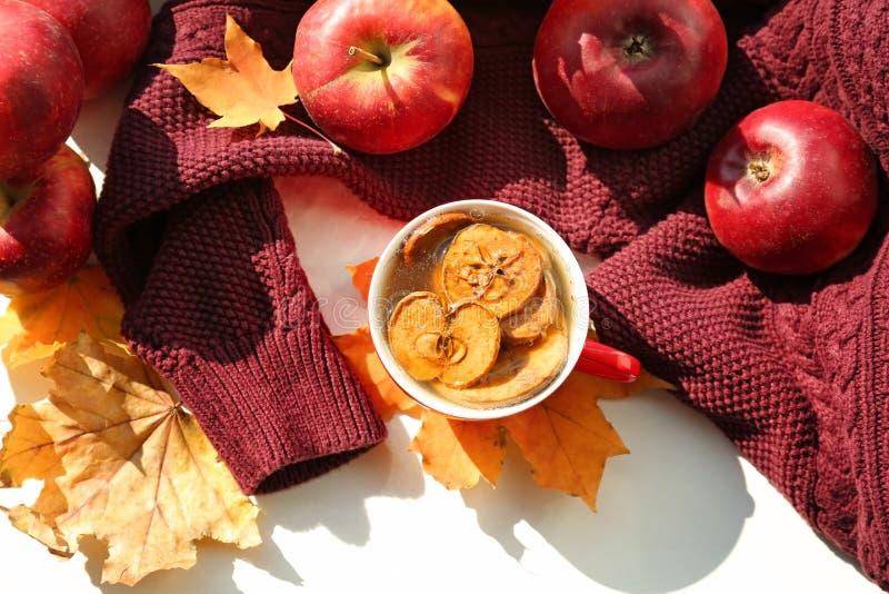 杯芳香茶用苹果和秋叶在白色桌上 库存照片