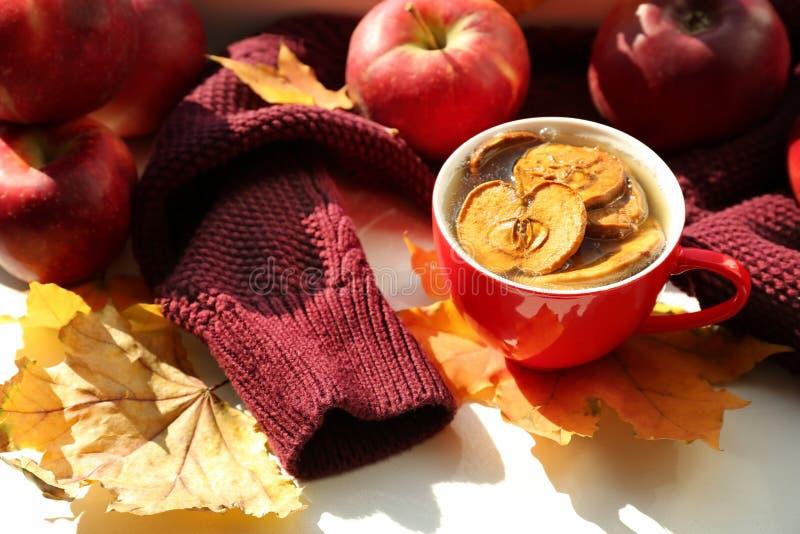 杯芳香茶用苹果和秋叶在白色桌上 免版税库存图片