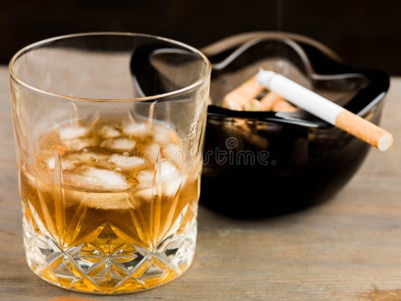 杯苏格兰威士忌酒和一根香烟在烟灰缸 免版税库存照片