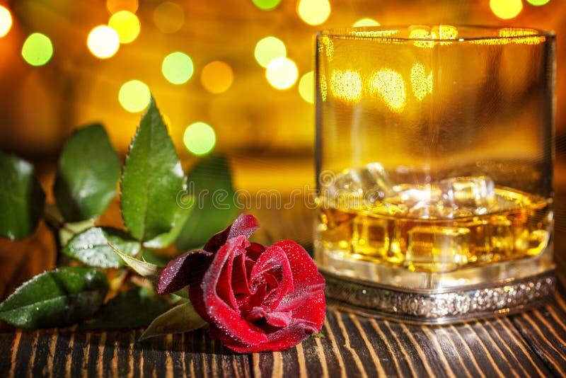 杯苏格兰威士忌酒和冰,在假日colorf的红色玫瑰 免版税库存图片