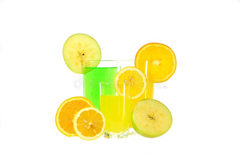 杯苹果、桔子和柠檬汁与切片结果实 免版税库存照片