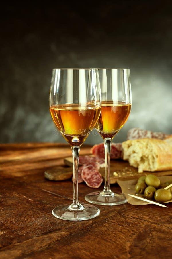 杯酒、被治疗的肉和橄榄在表上 库存照片