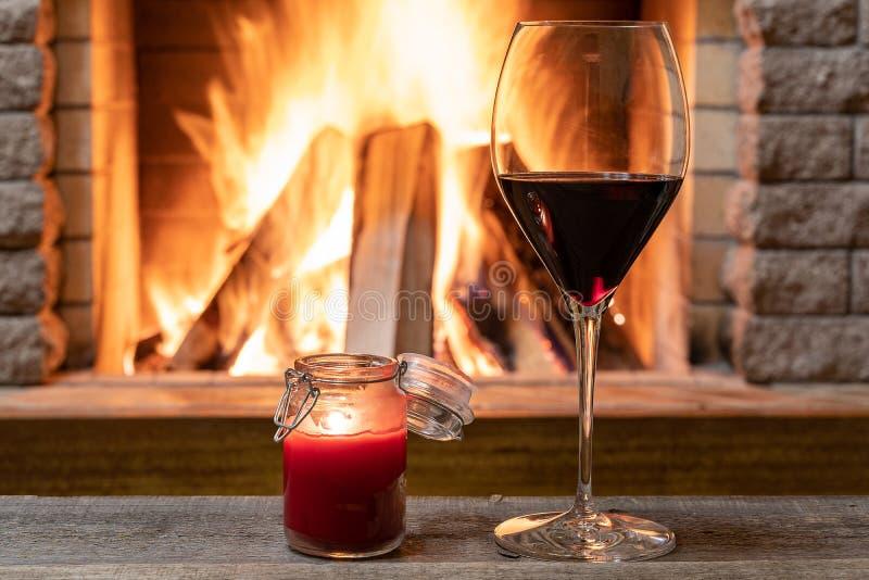 杯酒和蜡烛反对舒适壁炉背景,hygge概念 免版税图库摄影