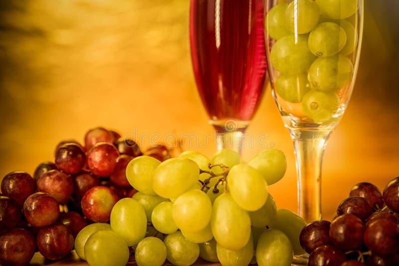 杯酒用在桌上的葡萄 免版税库存图片