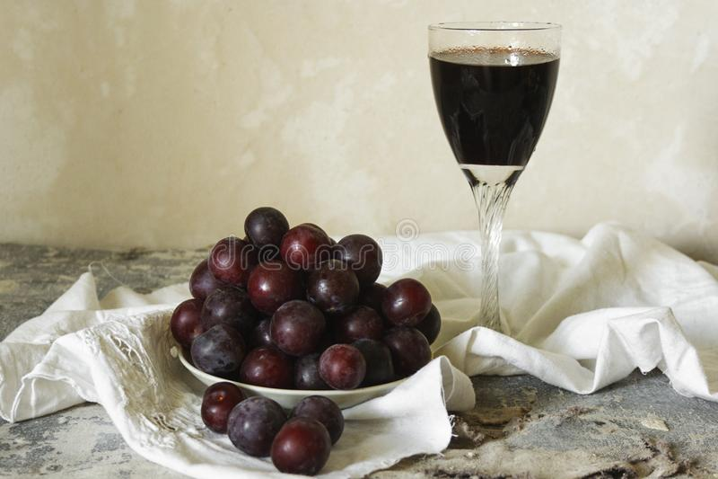 杯饭后葡萄酒和新鲜的李子板材在轻的背景的在土气样式 免版税图库摄影