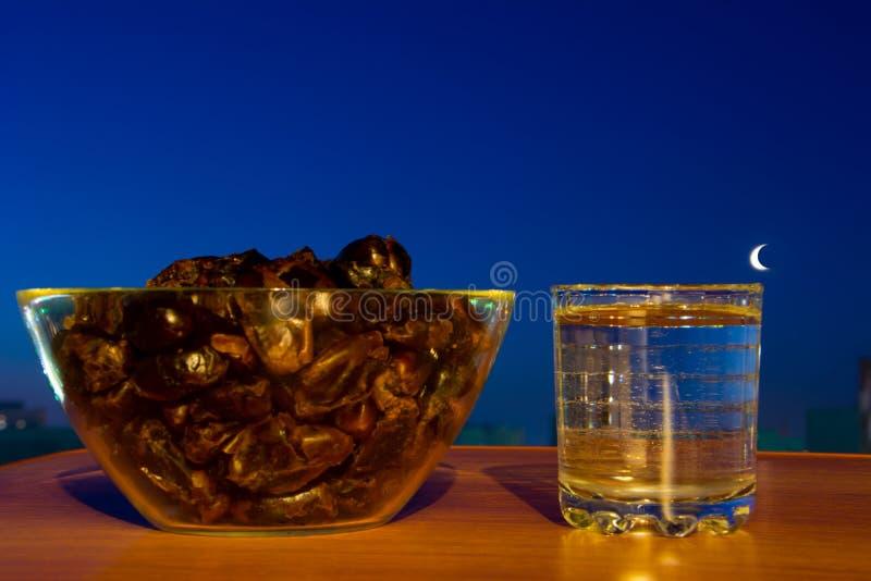杯饮用水、日期和月亮 基本的快速地打破斋月的食物和饮料 免版税图库摄影