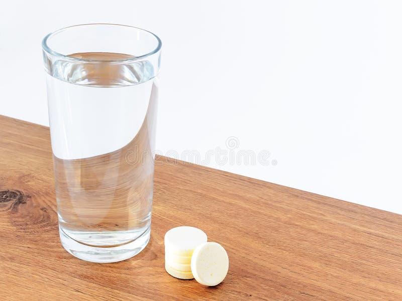杯饮用水和一些可溶解冒泡维生素药片在木背景与白色拷贝空间 维生素和 免版税图库摄影
