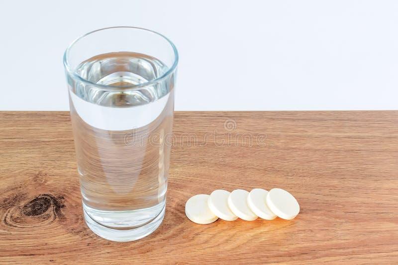 杯饮用水和五个可溶解冒泡维生素药片在木背景与白色拷贝空间 维生素和 库存照片
