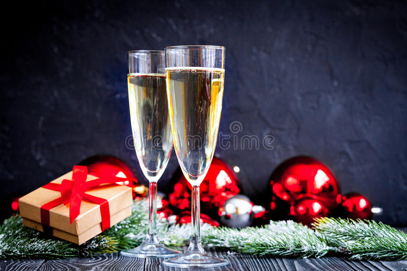 杯香槟和圣诞节装饰品在黑暗的木背景 免版税图库摄影