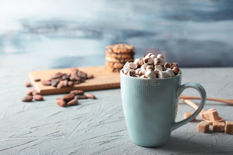 杯鲜美可可粉饮料用在织地不很细桌上的蛋白软糖 图库摄影