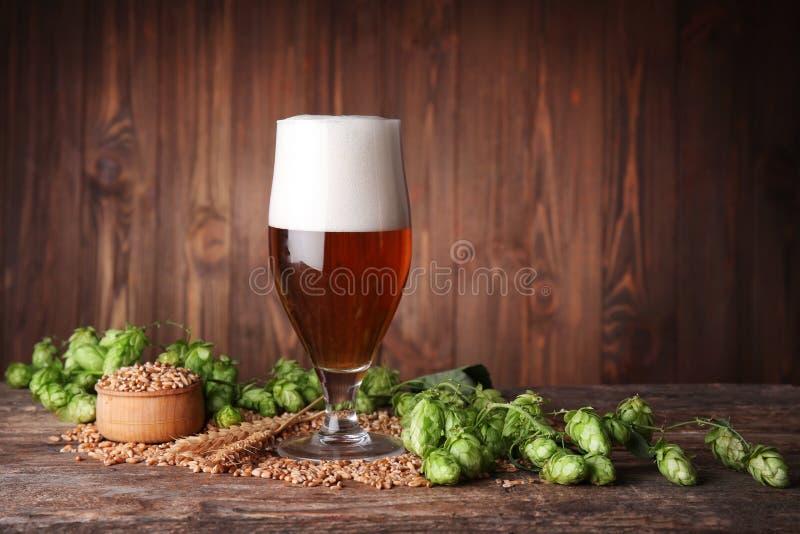 杯黑啤酒和成份在桌上反对被弄脏的木背景 库存照片