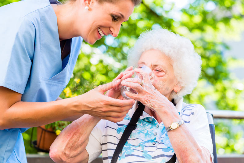 给杯水的老年医学的护士资深妇女 库存照片