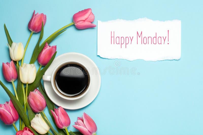 杯coffe和在蓝色背景的桃红色郁金香 词愉快的星期一 春天咖啡概念 顶视图,平的位置 库存图片