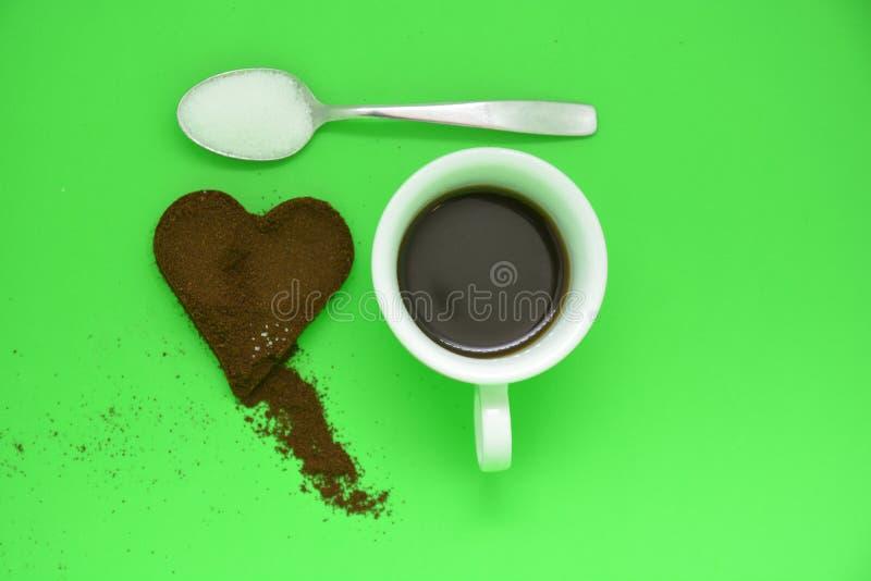 杯coffe和在金属匙子和coffe心脏的白糖 免版税库存照片