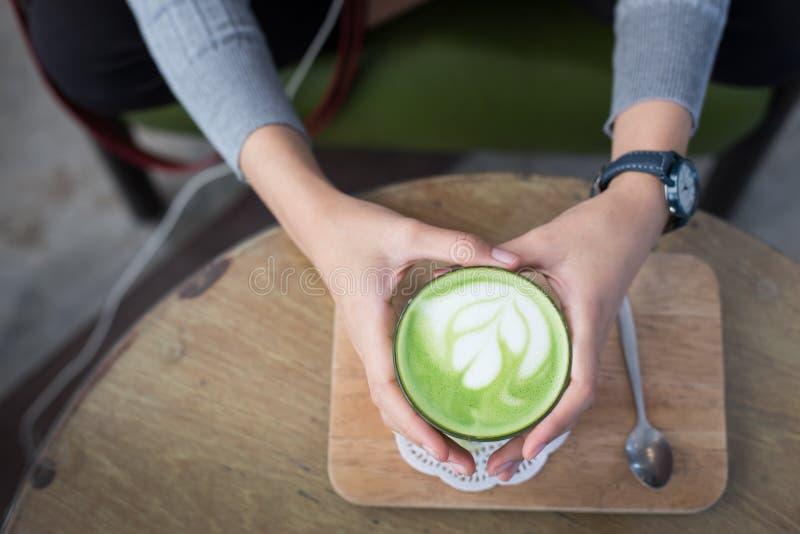 杯Matcha绿茶在妇女手上 库存照片