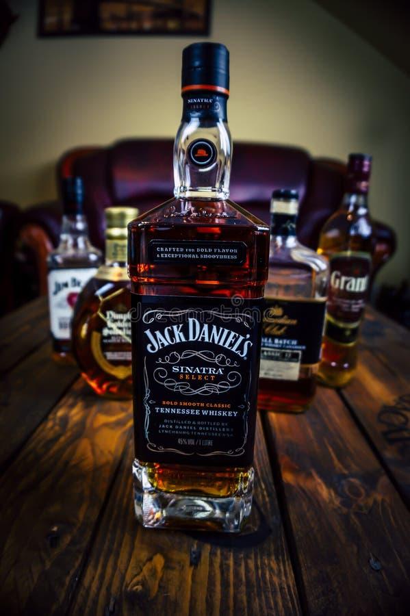 杰克丹尼尔的法兰・仙纳杜拉编辑在木板台桌上的威士忌酒瓶与其他威士忌酒瓶在背景中 库存照片