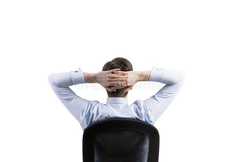 松弛商人的背面图在办公室椅子的 库存图片