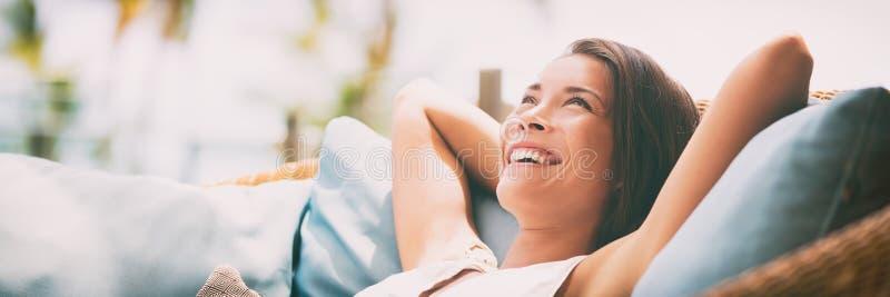 松弛家庭生活方式愉快的妇女放松说谎与在头微笑后的胳膊的豪华酒店房间沙发 亚裔女孩 库存照片