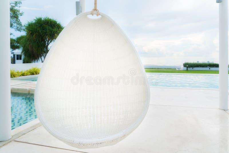 松弛白色在游泳池的藤条垂悬的椅子在海视图 免版税库存图片