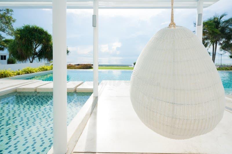 松弛白色在游泳池的藤条垂悬的椅子在海视图 库存图片