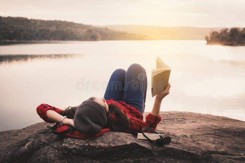 松弛读书的片刻亚裔游人在岩石 免版税图库摄影