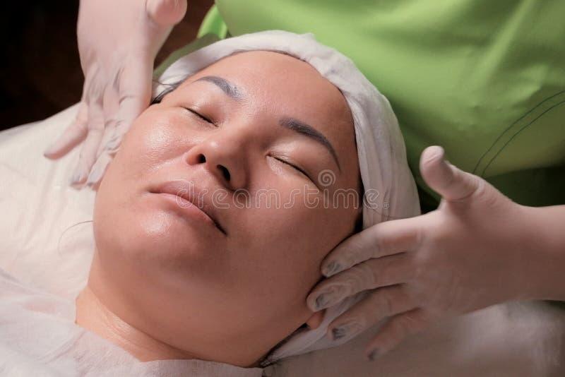 松弛面部按摩 女性cosmetological做法 一名美容师的手白色手套的在一个亚裔女孩的面颊 免版税库存图片