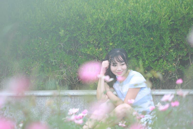 轻松的亚裔中国女孩在庭院里享受业余时间 免版税图库摄影