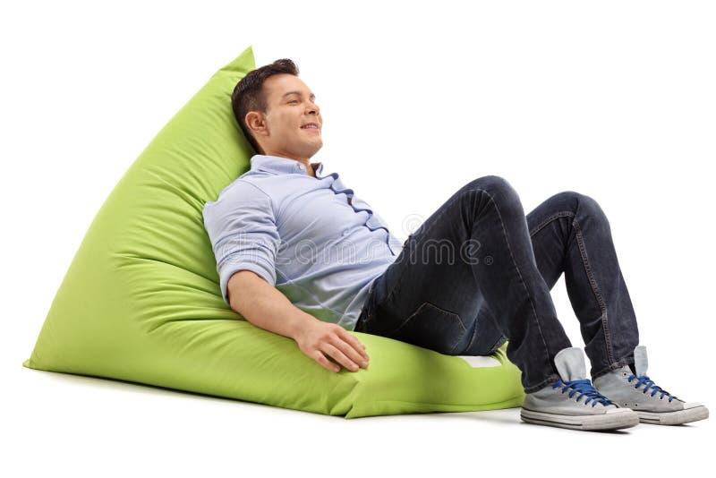 轻松的人坐装豆子小布袋 免版税图库摄影