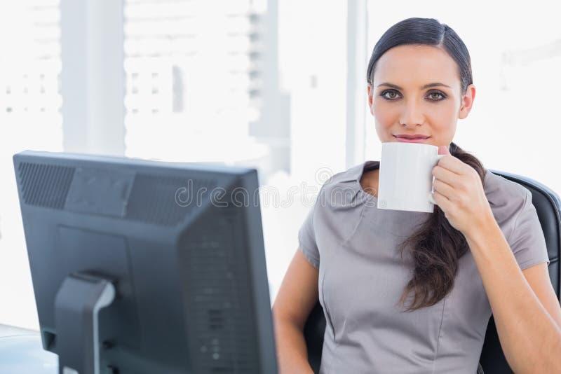轻松的可爱的女实业家饮用的茶 免版税库存图片