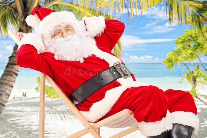 轻松的圣诞老人坐一把椅子,在海滩 免版税图库摄影