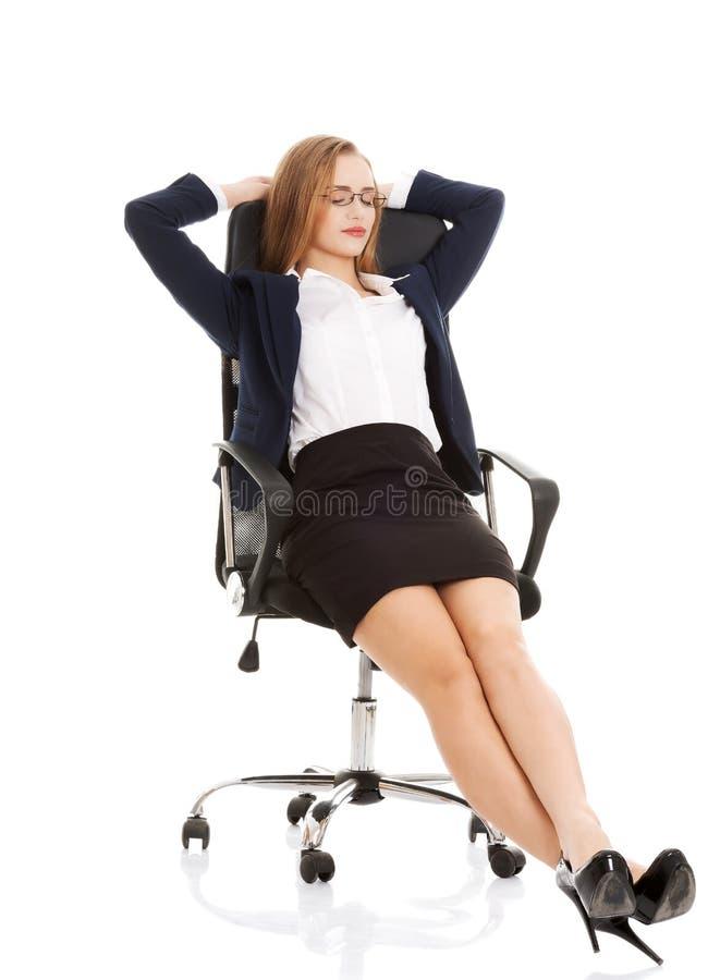 轻松的女商人坐与闭合的眼睛的一把椅子。 免版税库存图片