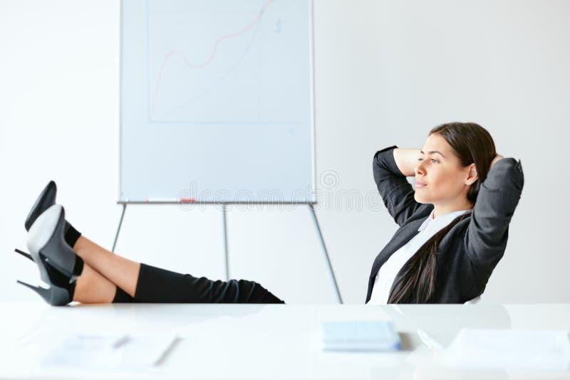 轻松的女商人画象与腿坐书桌 免版税库存图片
