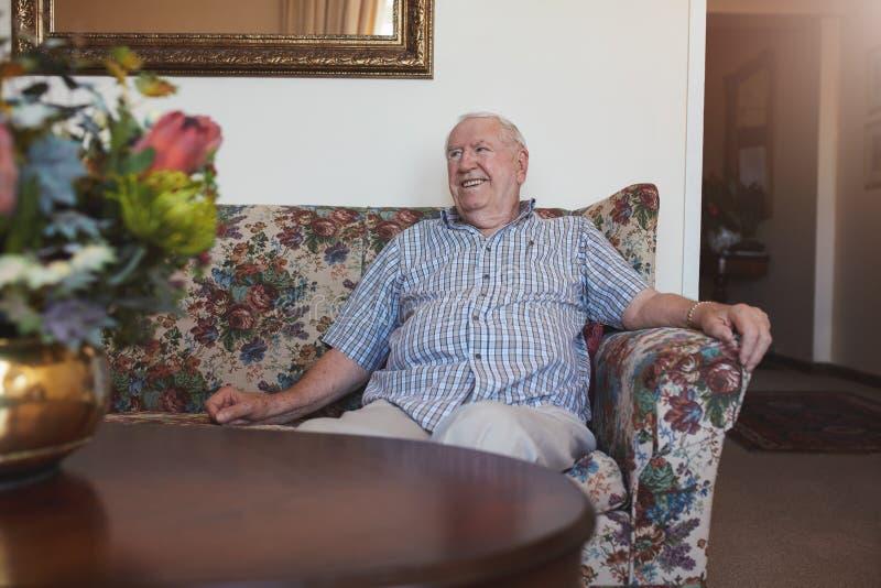 轻松的老人坐沙发 库存照片