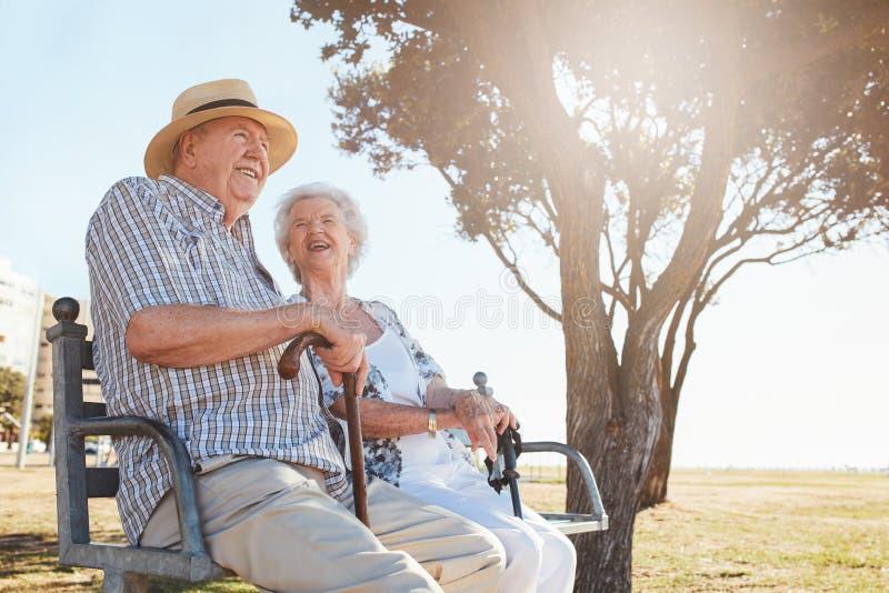 轻松的资深夫妇坐公园长椅 免版税图库摄影