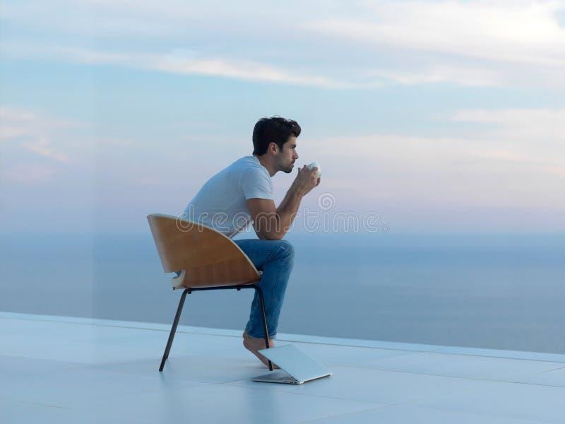 轻松的年轻人在家阳台的 库存照片