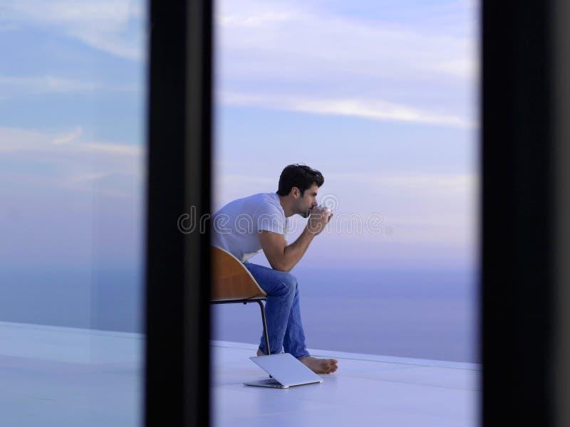 轻松的年轻人在家阳台的 免版税库存照片