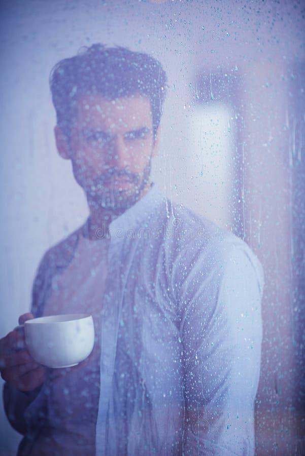轻松的年轻人饮料第一早晨咖啡withh雨滴下  库存图片