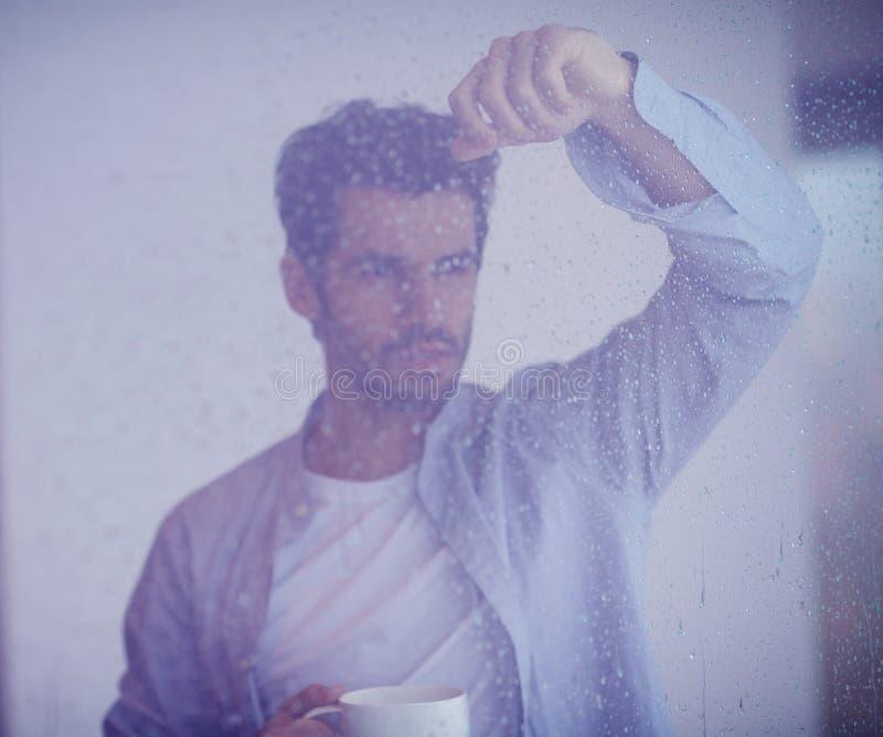 轻松的年轻人饮料第一早晨咖啡withh雨滴下  免版税库存照片
