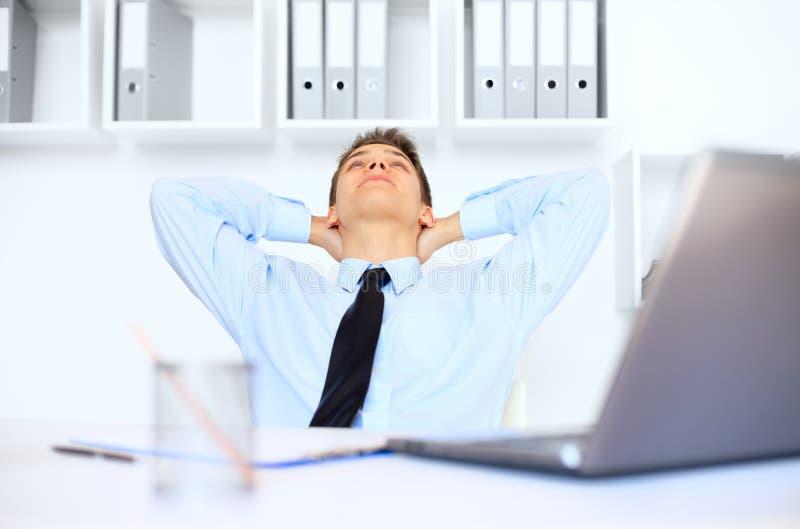 轻松的年轻商人在办公室 免版税库存图片