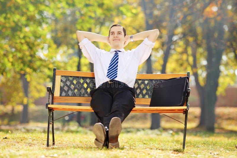 轻松的年轻商人坐一条长凳在公园 库存图片