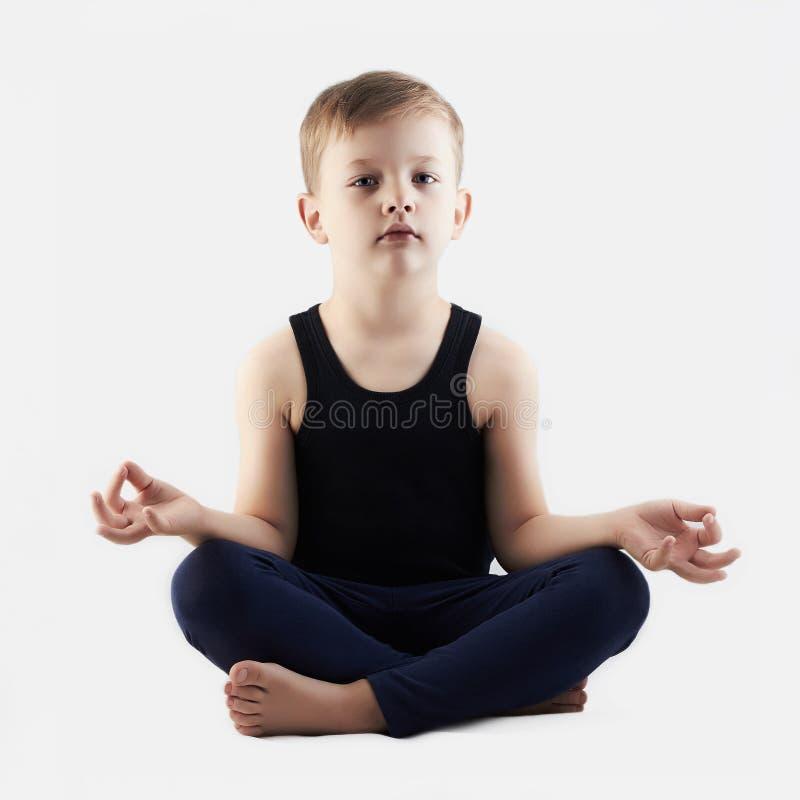 轻松的滑稽的儿童实践的瑜伽 小男孩做瑜伽 免版税库存照片