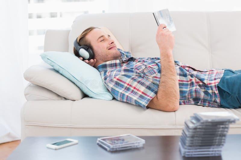 轻松的说谎在沙发的人听的音乐 免版税库存照片