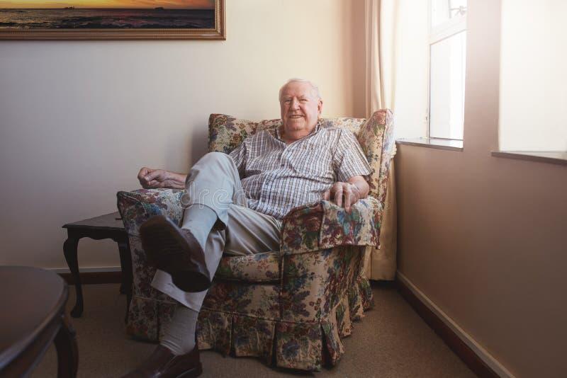 轻松的年长人坐胳膊椅子 库存图片